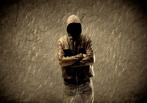 A man in a hoodie stands in a gray area covered in rain.